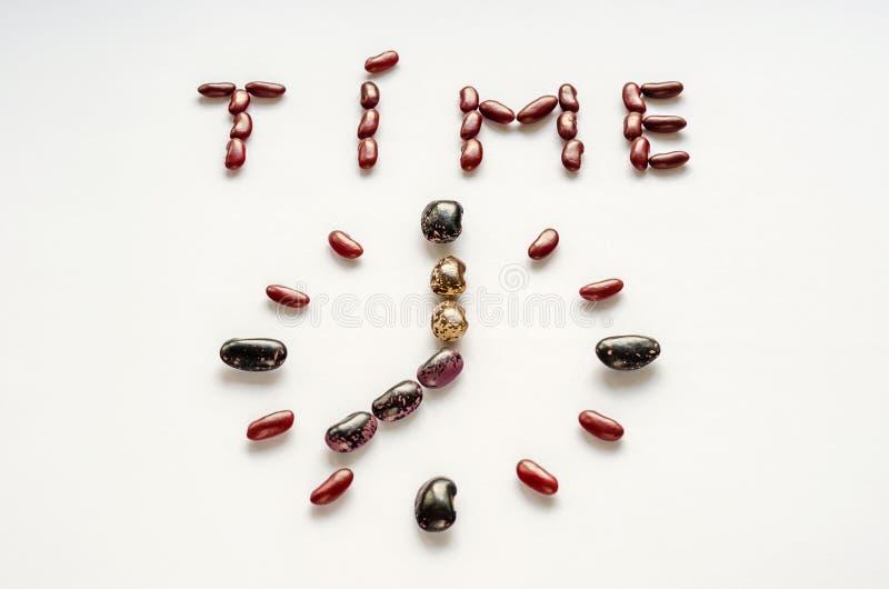 Temps de Word et visage d'horloge formé hors des haricots nains colorés sur le fond blanc Concept sain de consommation photo stock