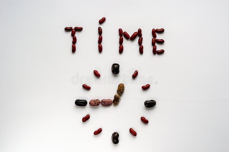 Temps de Word et visage d'horloge form? hors des haricots nains color?s sur le fond blanc Concept sain de consommation image stock