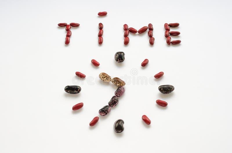 Temps de Word et visage d'horloge form? hors des haricots nains color?s sur le fond blanc Concept sain de consommation image libre de droits