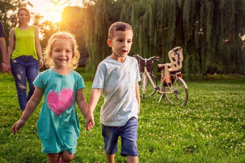 Temps dr?le - beaux enfants en bas ?ge marchant avec des parents en parc image libre de droits