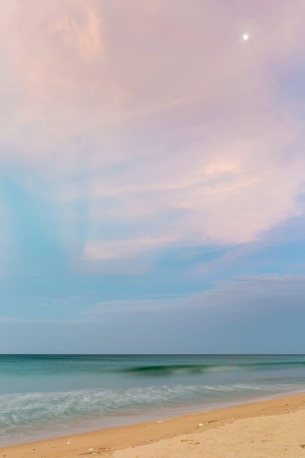 Temps en pastel de crépuscule sur la plage de désert avec la lune image stock