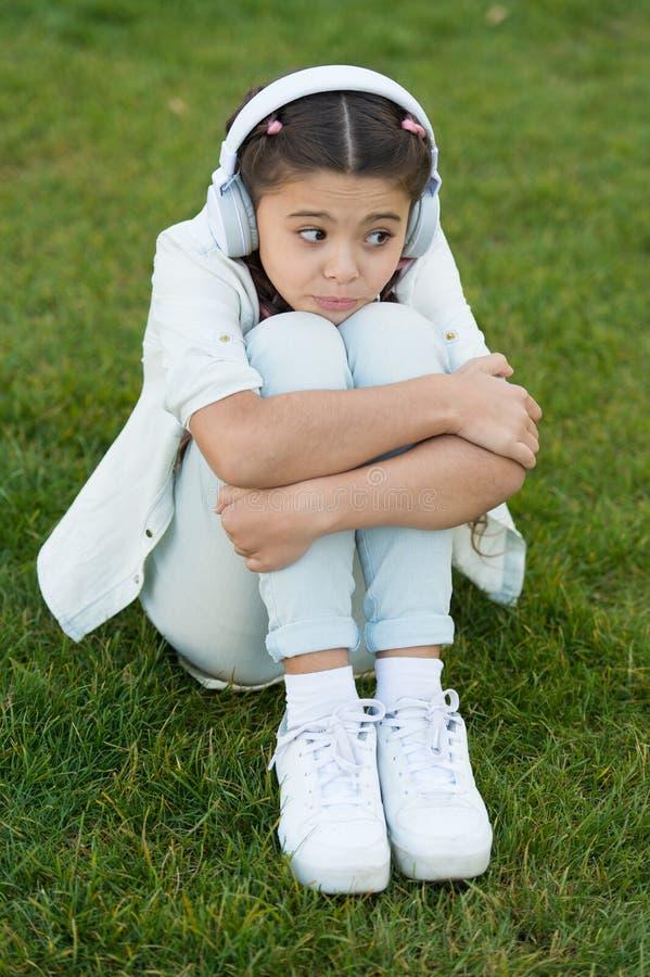 Temps libre agréable Les écouteurs d'enfant écoutent musique Façonnez la fille assez fraîche dans la musique de écoute d'écouteur photos libres de droits