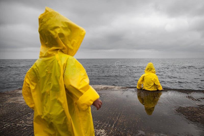 Temps nuageux pluvieux Deux enfants dans des imperméables jaunes photos libres de droits