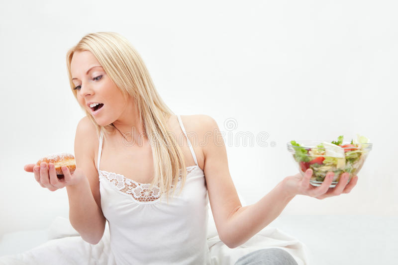 Download Tempted Young Woman Making A Food Choice Stock Image - Image of food, bite: 23254825