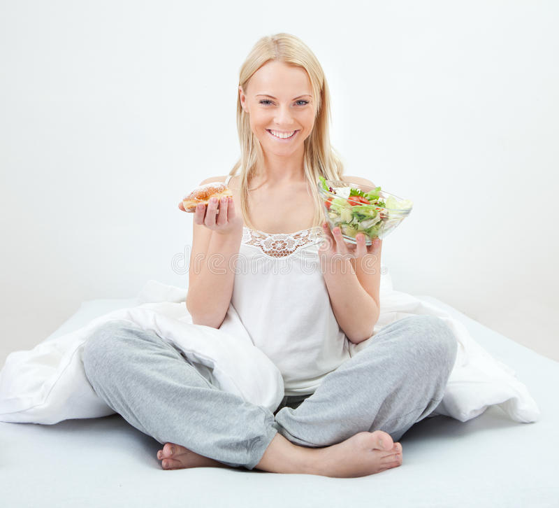 Download Tempted Young Woman Making A Food Choice Stock Photo - Image of hungry, holding: 23254838