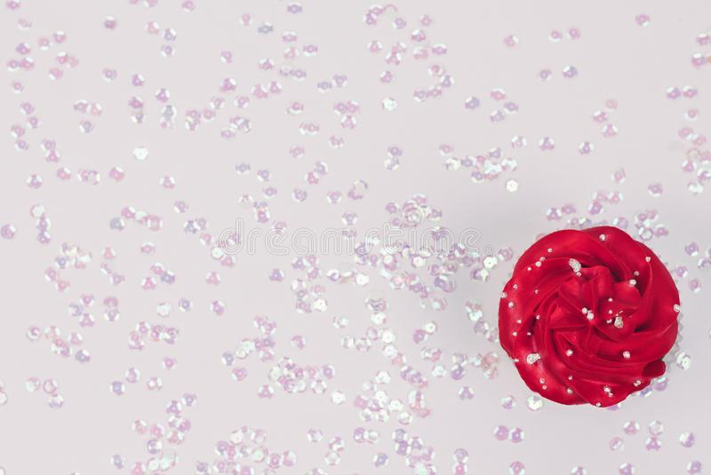 Cupcake with red icing on festive white background sprinkled with pearly confetti. Top view. Copy space. stock photography