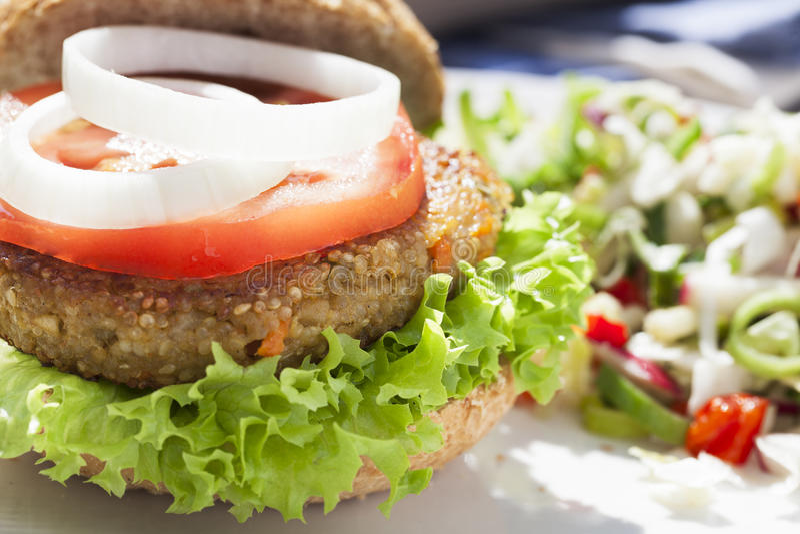 Tempting Veggie Burger. Tempting quinoa veggie burger with tomato and onion slices stock image