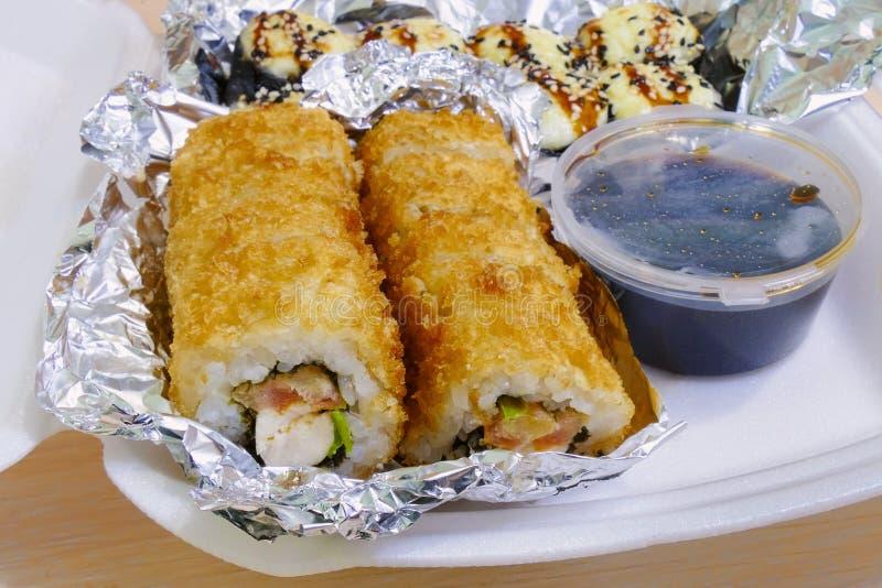 Tempura Maki Sushi - Fried Roll profundo com ckicken envolvido na folha para manter-se quente para a entrega fotografia de stock
