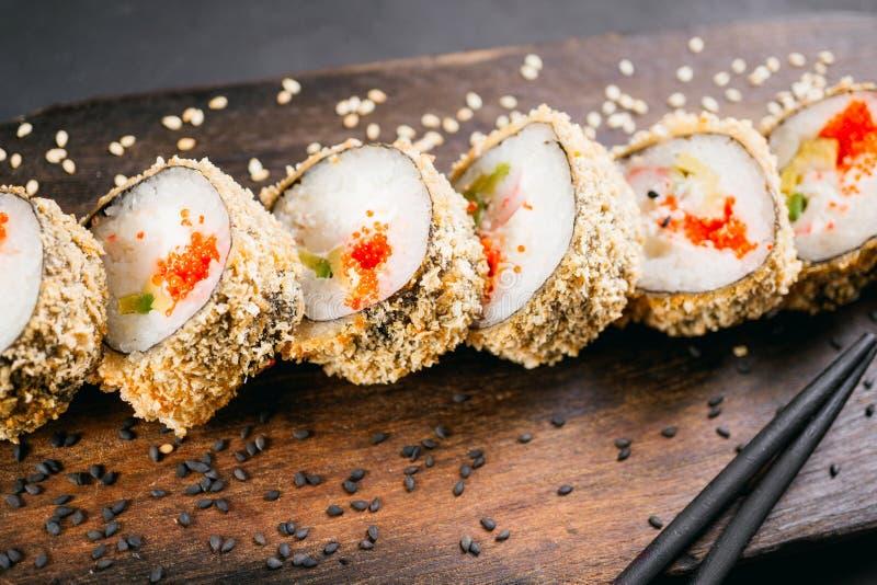 Tempura maki sushi roll on wooden platter. Japanese traditional fusion food style, restaurant menu stock photos
