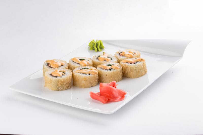 Tempura sushi maki roll with shrimp, avocado and mayo on top isolated on white background stock photography