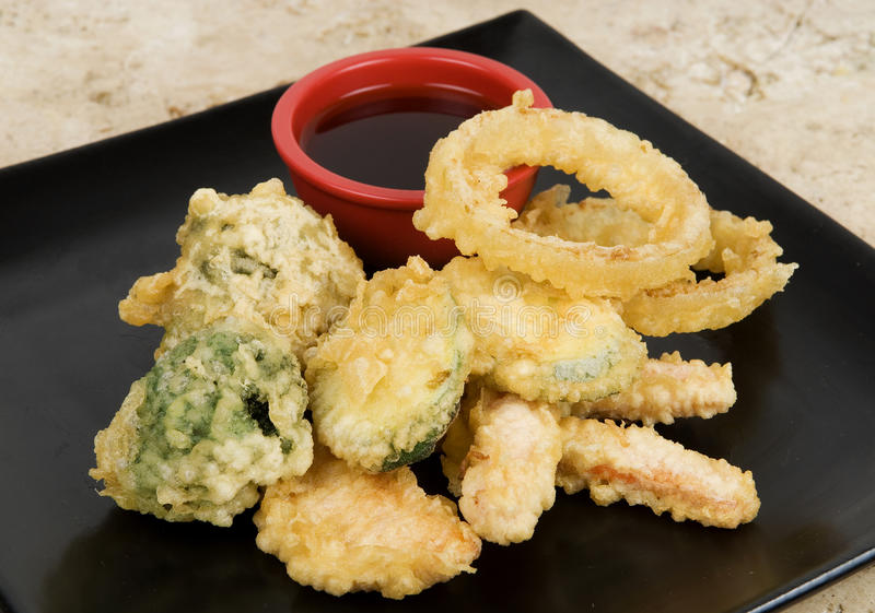 Tempura Vegetables. With Broccoli, Carrots, Zucchini, Onion Rings, Sweet Potato, Yam, Dipping Sauce, on Black Plate with Background, Asian crispy veggies royalty free stock images