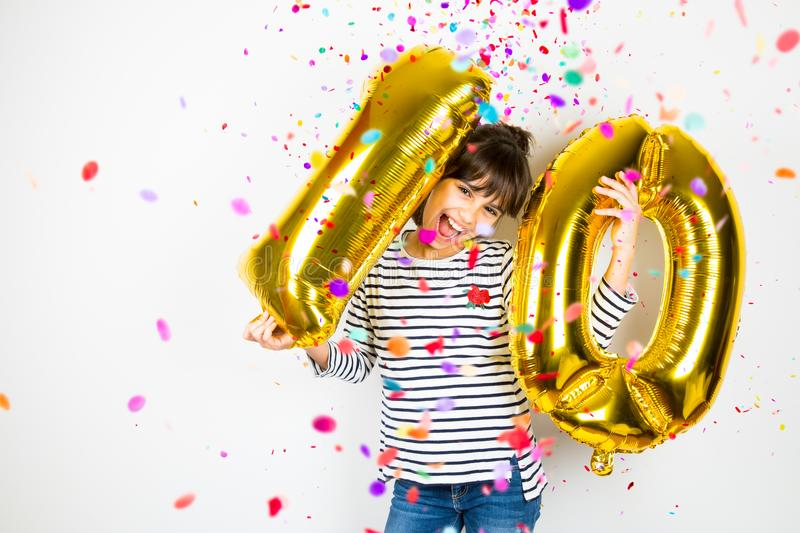 Ten birthday party girl with golden balloons and confetti stock photo
