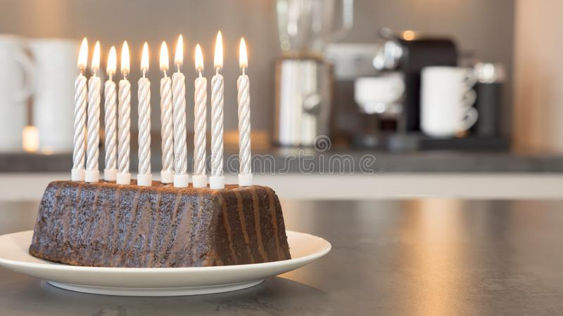 Ten burning candles on a birthday cake in a modern kitchen stock photo