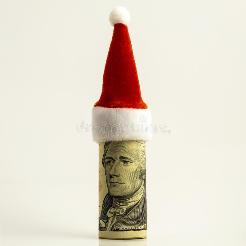 The ten-dollar bill is rolled up and the red Santa Claus hat at the top. New year surprise. Funny portrait of president Hamilton. royalty free stock image