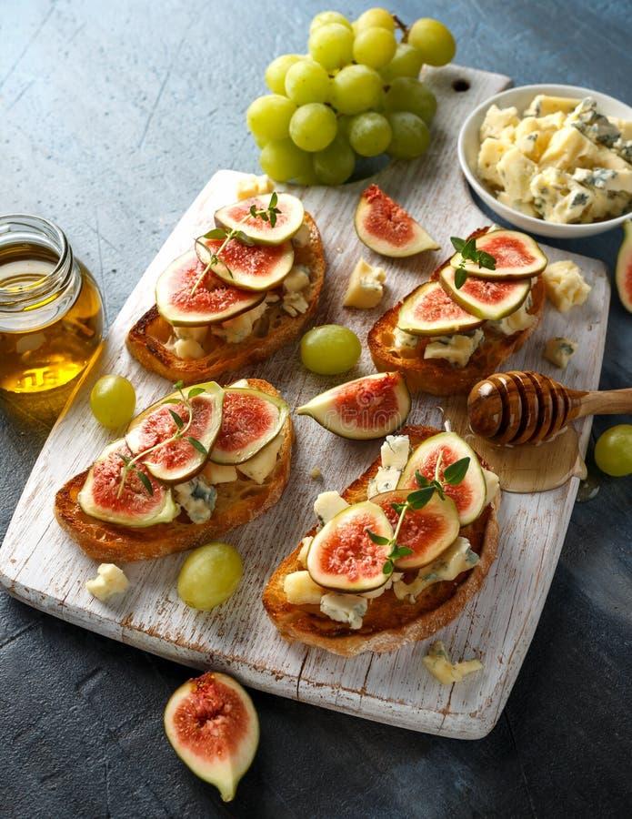 Ten figi i Gorgonzola tartines, grzanka, bruschetta mżący z miodem na białej drewnianej desce fotografia stock