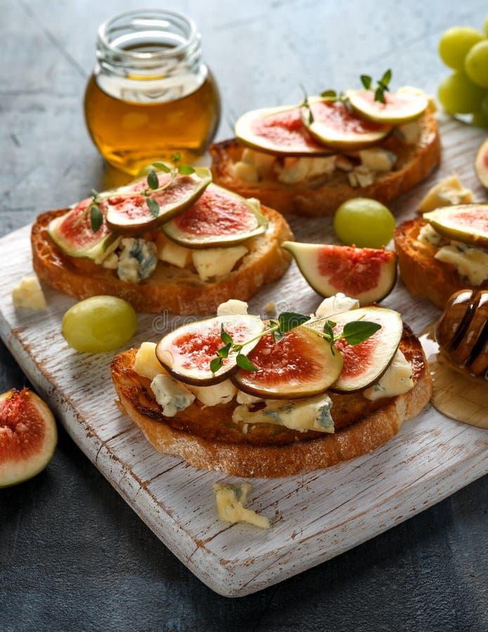 Ten figi i Gorgonzola tartines, grzanka, bruschetta mżący z miodem na białej drewnianej desce obraz royalty free