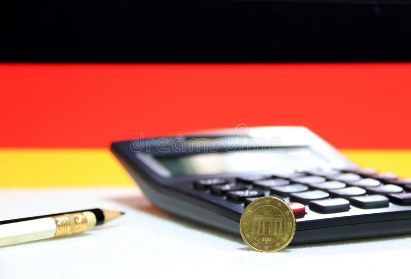 Ten Germany euro cent on obverse on white floor with black calculator and pencil, Germany flag background. Ten Germany euro cent on obverse on white floor with stock images