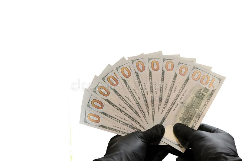 Ten hundred dollar bills and black rubber gloves. Thousand US dollars as a fan in male hands. Isolated on white background. Copy stock image