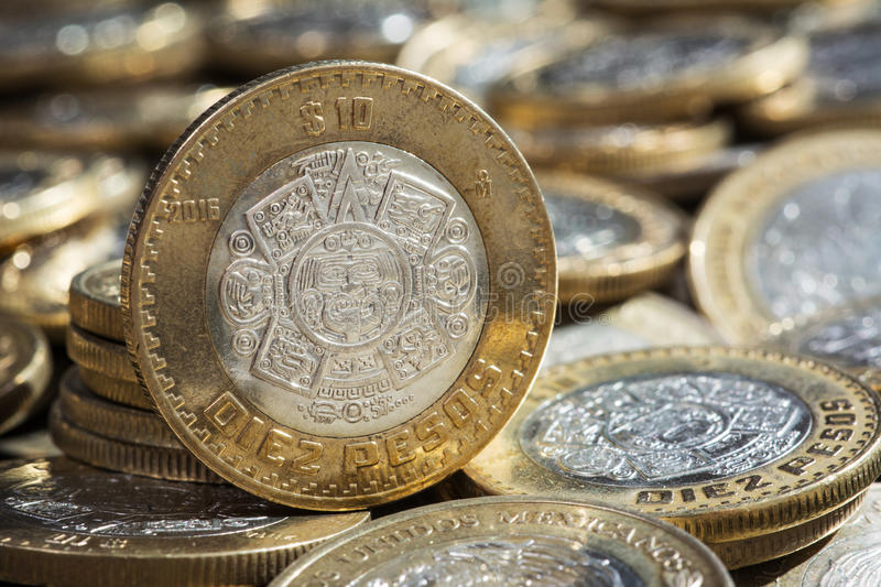 Ten Mexican pesos currency on more coins in disorder.  stock photos