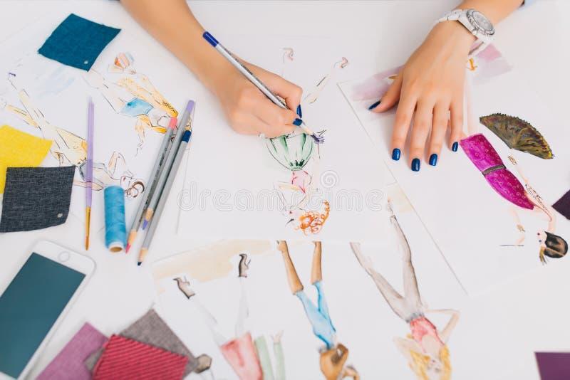 Ten obrazek opisuje procesy projektować odziewa Tam są ręki dziewczyna rysunku nakreślenia na stole zdjęcie royalty free