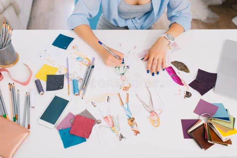 Ten obrazek opisuje procesy projektować odziewa Tam są ręki dziewczyna rysunku nakreślenia na stole zdjęcie stock