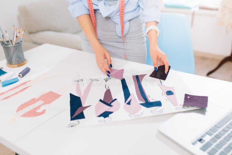 Ten obrazek opisuje procesy projektować odziewa w warsztacie Tam są ręki dziewczyna szuka zdjęcia stock