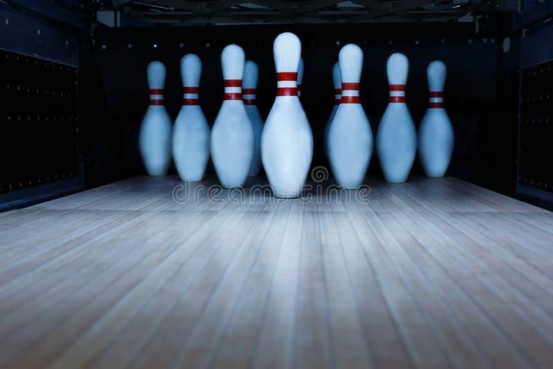 Ten pin bowling alley background. Closeup of tenpin row on a lane, night light stock image