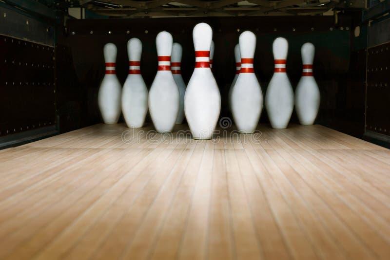 Ten pin bowling alley background. Closeup of tenpin row on a lane, night light royalty free stock photo