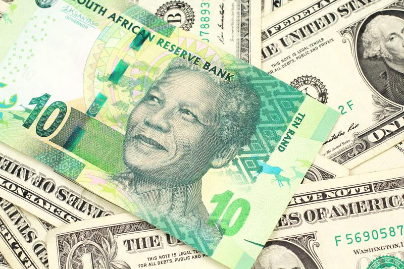 A ten South African rand bank note on a bed of American dollar bills. A close up image of a green ten rand bank note from South Africa in macro on a bed of royalty free stock photography
