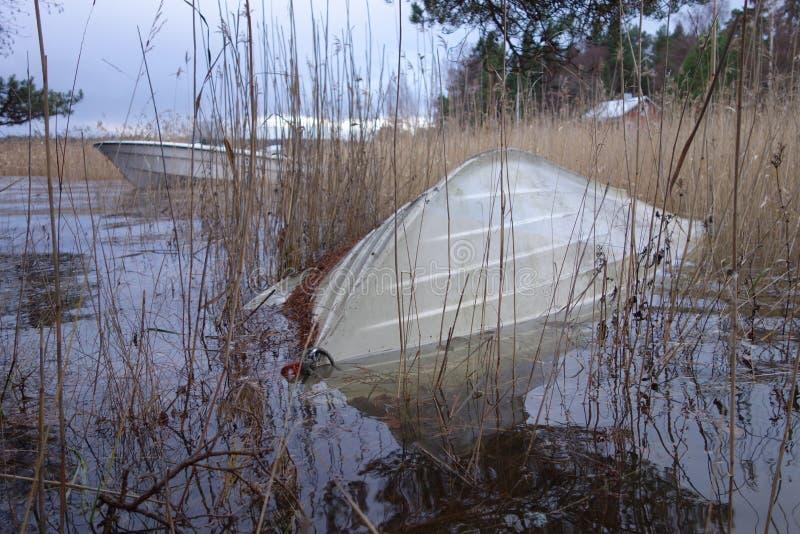 Ten val gebrachte roeiboot gedeeltelijk onder vloedwater stock foto's