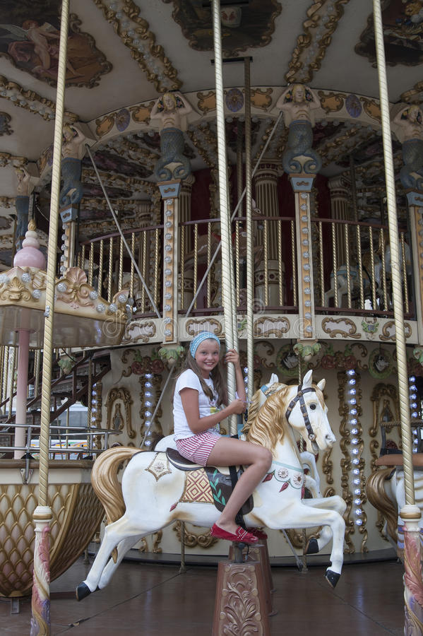 Ten-year girl riding a classic French carousel. Десятил royalty free stock photography