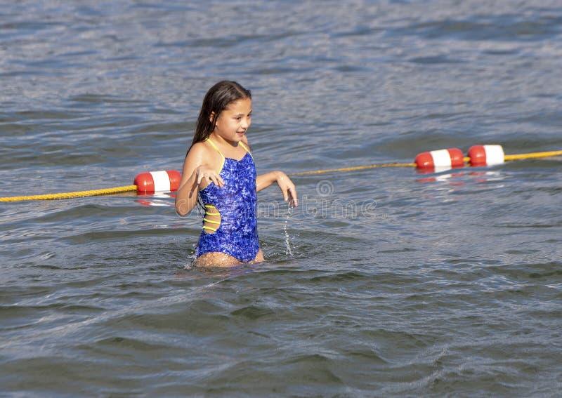 Ten year old Amerasian girl having fun in the lake at Greenlake Park, Seattle, Washington. Pictured is a smiling ten yearold Amerasian girl having fun on stock images