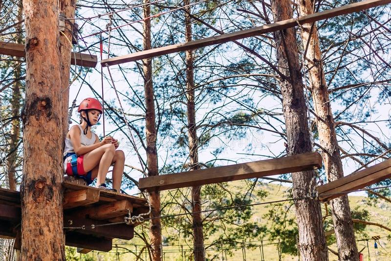 Ten-year-old girl in a helmet on a rope town outdoors in the summer. Rest before the passage of obstacles. To overcome fear stock photos