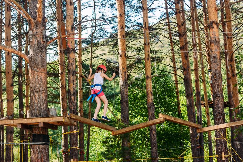A ten-year-old girl in shorts, a t-shirt and a protective helmet passes through the rope Park.. Extreme sports on top stock photo