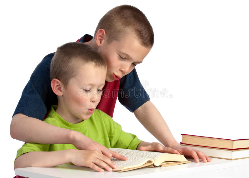 Ten-year-old teching his kid brother to read. Blond, young, happy brothers, one ten years old, the other six, working together with kid brother's reading royalty free stock image