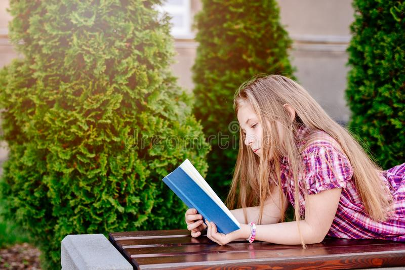 Ten years old blue eye blonde girl reading book. At the bench royalty free stock photo