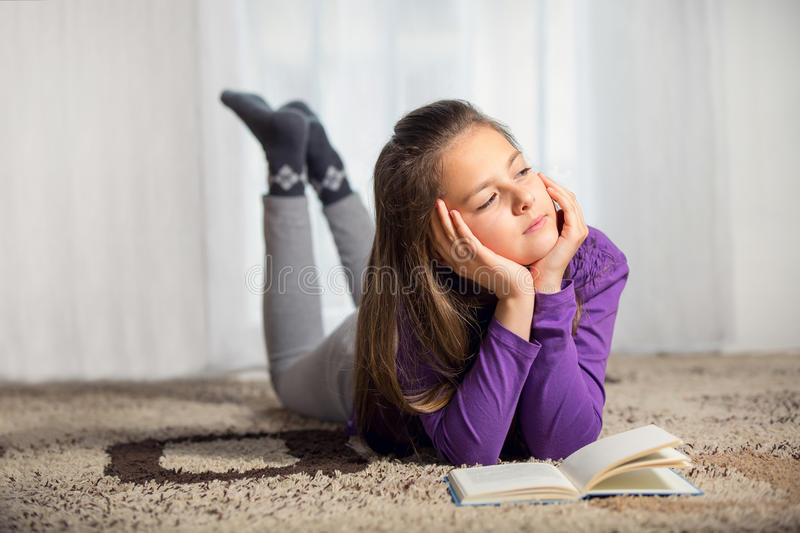 Ten years old girl with a books. Iat home royalty free stock photography