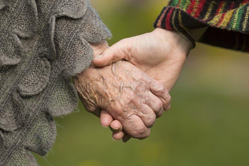 Tenant des mains ensemble - vieux et jeune Amour images libres de droits