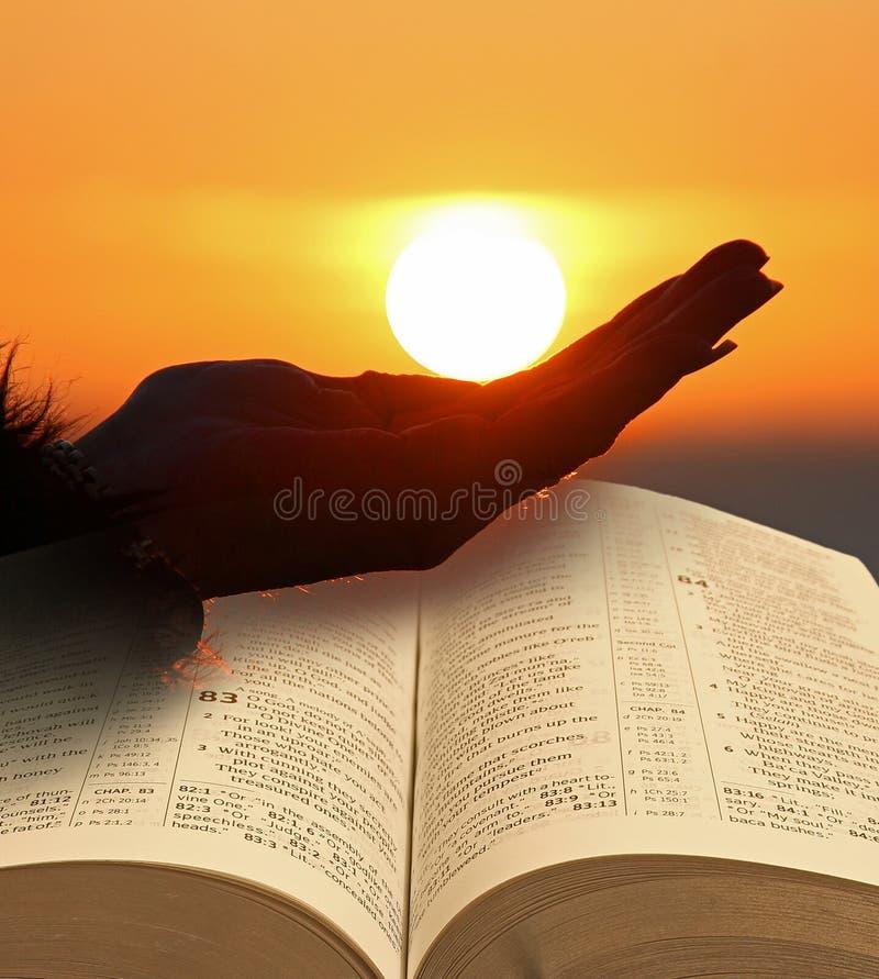 Tenant le soleil à disposition avec la Sainte Bible ouverte photographie stock libre de droits