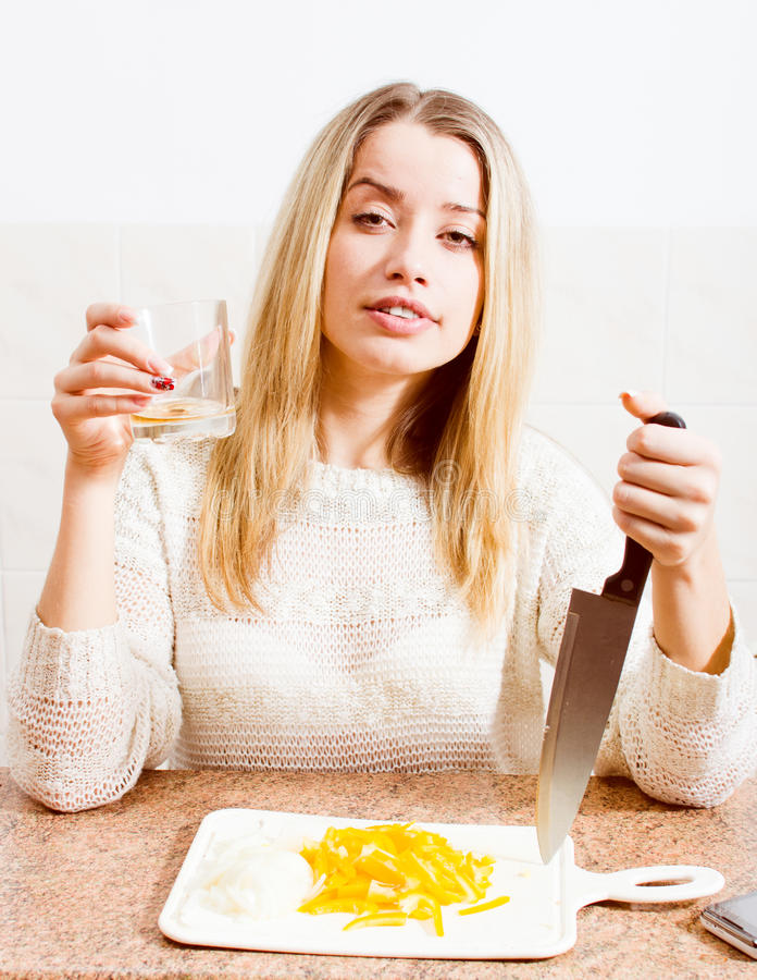 Tenant un couteau sa main et en ayant jeune femme blonde potable de boisson d'amusement la belle avec la détente de yeux verts images libres de droits