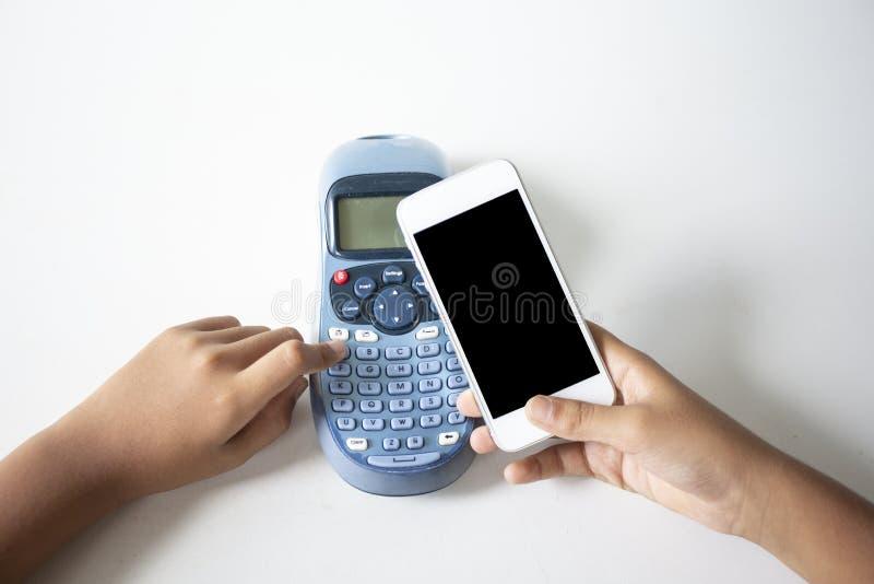 Tenant une carte de cr?dit et ?crire le code de s?curit? utilisant un ordinateur portable, smartphone en ligne d'appli de paiemen images stock
