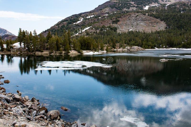 Tenaya See mit teilweisem Eis auf dem ruhigen Wasser während des Sommers Dieser alpine See ist in Yosemite Nationalpark lizenzfreies stockbild