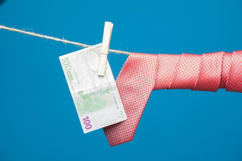 Tenazes de brasa, dinheiro e laço com nó, em uma corda imagens de stock