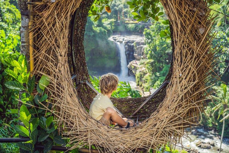 Tendência de Bali, ninhos da palha em toda parte Lugar amigável da criança Turista do menino que aprecia seu curso em torno da il foto de stock royalty free