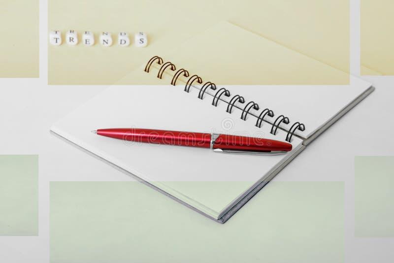 Tendências reais Bloco de notas e pena Letras em uma superfície branca imagens de stock