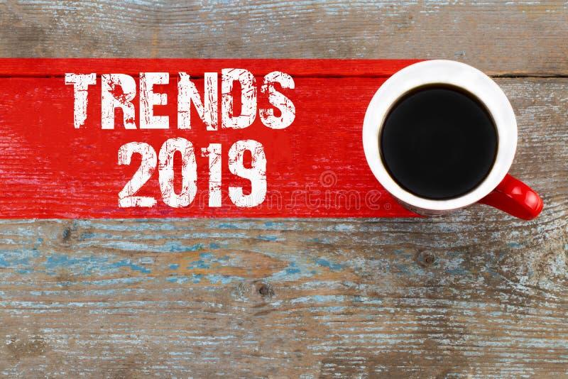 Tendências 2019/xícara de café com inscrição das tendências em vagabundos de madeira imagem de stock