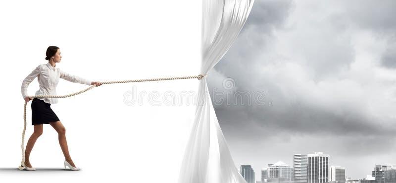 Tenda bianca d'apertura della giovane donna e presentare il paesaggio moderno della città immagini stock