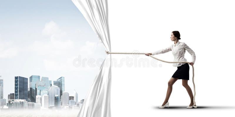 Tenda bianca d'apertura della giovane donna e presentare il paesaggio moderno della città immagine stock