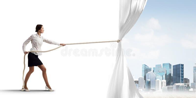 Tenda bianca d'apertura della giovane donna e presentare il paesaggio moderno della città immagine stock libera da diritti
