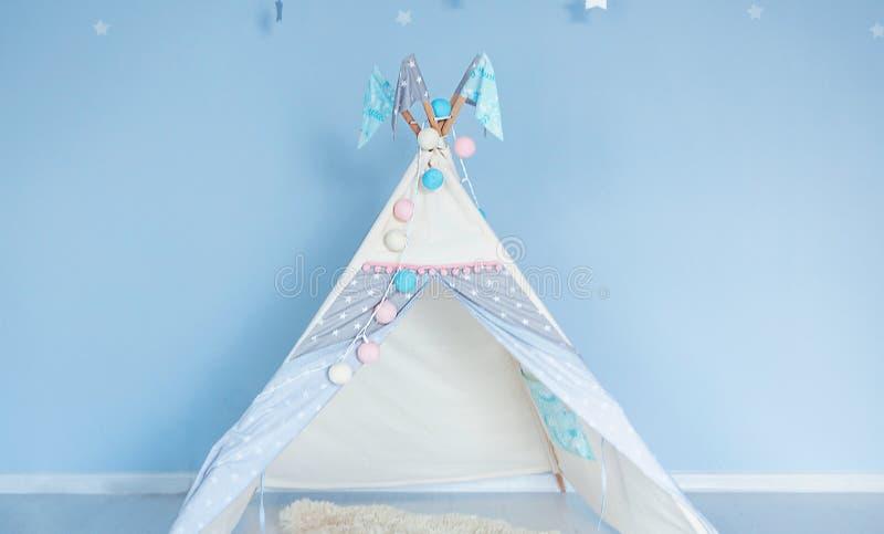 Tenda del giocattolo nella stanza dei bambini sui precedenti della parete blu fotografia stock